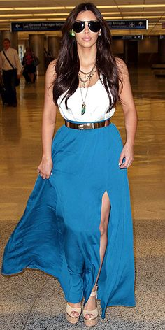 KIM KARDASHIAN  Flashing skin may make sister Khloé nervous, but Kim confidently flaunts her assets in a sexy white tank, high-slit teal maxi skirt and eye-catching metallic accessories for her Miami arrival.