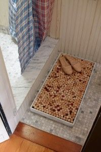 A shadowbox frame from Michaels, painted white, and filled with 500 or so wine corks as an eco-friendly, very cushy bath mat.     No glue, no fuss… just the tension of the corks is enough to keep it full and taut.