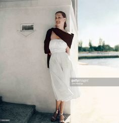 Model wearing stiff white cotton dress by Claire McCardell and black silk shawl…
