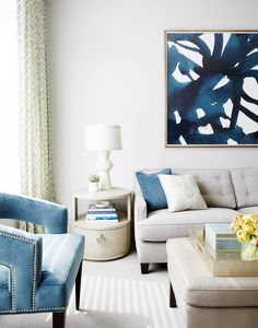 Tan furniture is mixed with blue hued cushions and chairs and matched with a white lamp and a big painting