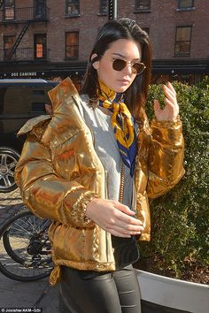 Glam: The model covered her eyes with gold-rimmed sunglasses and left her brunette tresses...