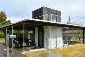 お隣は柿畑 神奈川県の西部、東海道線の駅を降りて10数分ほどの住宅地の一角に畑と緑の広がる場所がある。板倉邸はその場所に隣接して立っている。 敷地の2辺が生産緑地に面し、隣は柿畑、少し先には竹林も見えるという、住宅地にしては珍しいロケーションなのである。そうした環境の中、4面をすべてガラス張りにした外観が異彩を放っているが、だからと言って、自らの存在を強く主張するような姿勢はいささかも感じられない。その理由のひとつに、屋根面が低く抑えられていることが挙げられるだろう。 床面を下げてつくる 中央部分を除くとほぼ平屋建てと言ってもよいこの家は、全体を70㎝掘り込んだ上に建てられているのだ。ポイントは、隣にある柿畑だった。夏になると葉が鬱蒼と茂り、ふつうに建てたのではせっかくの好立地にも関わらず、ちょうどその緑の部分に遮られて視線が抜けていかないのだ。…