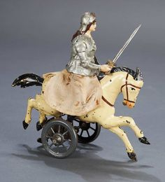 """6.5"""" German painted tin mechanical toy by Siegfried Gunthermann, late 19th century. When wound, the horse moves along on the wheeled base, and she (Joan of Arc? Bodica?) bobs up and down. Rare."""