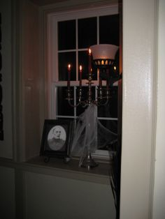 Creepy Halloween changing portrait and candelabra with blood-red candles and spider web.