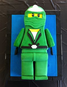 "Green Ninjago - I made this cake for a five year old boy. He had a tae kwon do party and the Sensei cut the cake in half with a sword. The sculpted cake is white and wrapped in fondant. I made a mold out of a 3"" X 5"" piece of Lego and rolled fondant into the mold to make each piece for the cake board background."