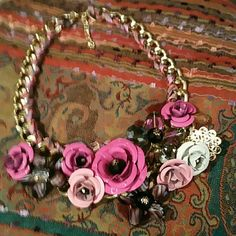 Roses and bead flower necklace Beautiful gold tone necklace with colorful ribbon wound through the chain. Metal roses are a medium pink, soft pink and white combined with some dangling beads. Interspersed are purple and smokey bead flowers. Perfect for spring. NWOT. Jewelry Necklaces