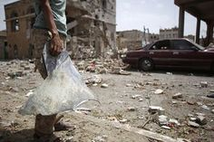 A Shia Houthi rebel holds up a fragment of metal next to the rubble of houses destroyed by a Saudi-led airstrike in Sanaa, Yemen