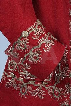 Detail sleeve, frock coat, Scotland, c. 1745-1750. Scarlet superfine wool, elaborately embroidered with gilt thread and sequins, the buttons covered in interwoven metal strip, lined in crimson silk, with densely embroidered broad pocket flaps, decorative buttons to the sword slits.