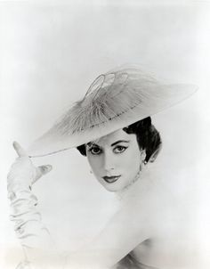 This 1953 photograph of a model wearing a chiffon and feather hat, called The Most Beautiful Day of the Year is part of a set of prints from the studio of New York celebrity milliner, Mr John. The print was produced to promote Mr John's 1953 Coronation of Spring and Summer Collection