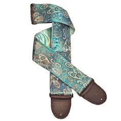A delicious, stunning artisan handmade guitar strap of rich turquoise and shimmering gold and silver! The front fabric of the guitar strap is thick, lush turquoise satin brocade woven through with iconic paisleys, lotus blossoms, leaves, vines, and tendrils in shades of dazzling gold and bright silver. Scalloped leaves, flowers, and images-within-images so typical of India art and textiles fill the full length and virtually every open space of the guitar strap, creating an impression of ...