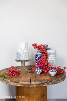 blue and white modern cake with pink bougainvillea, blue and white tall jars for a wedding dessert display