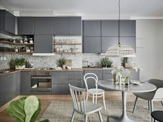 Grey kitchen cabinets in a Swedish space. Stadshem.