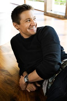 Jeremy Looking Sideways and Smiling Wearing Black Shirt and Pants and Watch on Left Wrist