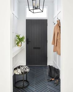really cute way to fake a mudroom. Dark ceramic tiles in a herringbone pattern make this entry feel so special. There might not be room for a console or a bench, but this small space solution is right right with a built-in counter, tuck away stool, and then coat hooks on the other side. You can perch things on the counter and throw keys on it.