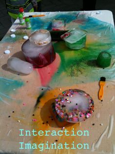 "Suzanne taped an old sheet onto a table & blocks of coloured ice are placed on, to create a piece of art as the ice melts & creates beautiful patterns - from Interaction Imagination ("",)"