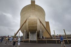 Visitors roam around a replica Noah's Ark as rain clouds pass overhead at the Ark Encounter theme park during a media preview day, Tuesday, July 5, 2016, in Williamstown, Ky. The long-awaited theme park based on the story of a man who got a warning from God about a worldwide flood will debut in central Kentucky this Thursday. The Christian group behind the 510 foot-long wooden ark says it will demonstrate that the stories of the Bible are true. Its construction has rankled opponents who say…
