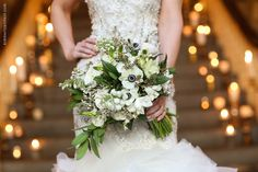 close-up shot of a bride holding a white and green bridal bouquet in front of a staircase full of candles  Photo by Kimberly Potterf