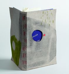 Ana Möbius <br> France <br><br> Visible sewing binding, red linen thread. Linen and blue calfskin. Decor : acetone transfers, linocuts. Circular opening in upper board. Titled in ivory foil. <br> Copy: 29/75 <br> Class of 2013 <br><br> <i>Photo : Michèle Garrec</i>