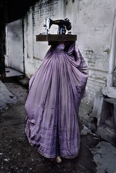 An Afghan refugee carries her sewing machine in Peshawar, Pakistan.  (2013)