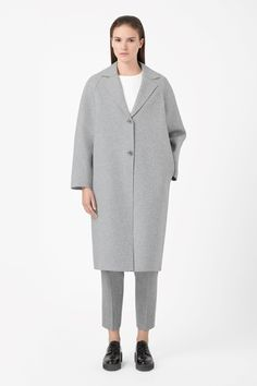 Made from unlined wool-mix jersey with a lightly structured quality, this oversized coat has clean raw-cut edges. A loose, relaxed fit with dropped shoulder seams, it has long raglan sleeves and a two-button fastening on the front.