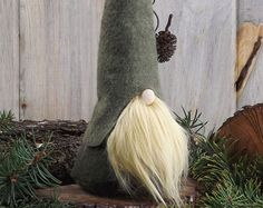 HADMAR the SILENT is a woodland gnome known by many as being a bit sneaky. He can find his way through the quiet forest without being heard or seen.  He is approximately 8 tall with a 3.5 bottom that is sewn and stuffed. He has a whimsical and unique look because the bottom of the base extends just slightly out towards the back, which I call the bum effect. Ive received so many customer comments on the design! Body is dark forest green with your choice of hat and beard color. Made from wool…