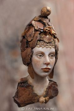 This haunting 5.5″ wall piece is sculpted polymer with bark and other inclusions. Wooden Spirit Amira was made by Tatjana Raum (Chopoli) in Germany. Her woodsprites bring with them bits of bark and leaves from the forest and smell slightly of moss.  Tatjana says she has always been fascinated by faces, painting and photographing them until she discovered sculpting. She creates art dolls and what she calls wooden spirits using either ceramic, paper or polymer clay.