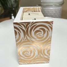 Wooden block perpetual calendar, hand-painted white with gold and white patterned paper. Set includes two blocks for the date and 3 wooden bars for the corresponding month, all of which are accented with cream colored paper and are stenciled with brown numbers.  Each calendar is 4-1/4 x 2 x 3 inches.  The white, cream and gold colored calendar offers a neutral element to any decorative theme. Also works well in both office and home spaces