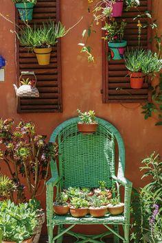 Patio rústico en terracota con toques de color verde y violeta, lleno de plantas en macetas de objetos reciclados. #balconplantas