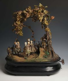 Victorian automaton with musical clockwork movement with six dolls dancing to a fiddler's tune under arbour, with glass dome (broken) and oval ebonised base on bun feet, 57cm high, sold at action for £ 1600.