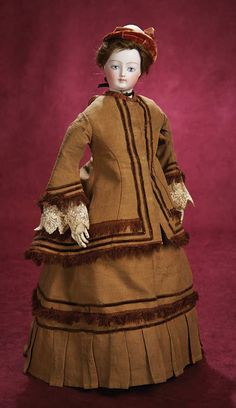 French Bisque Painted Eye Poupee, ca 1870, wearing a beautiful antique linen costume with brown velvet banding and silk fringe,velvet bonnet,undergarments,leather boots.