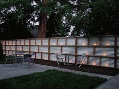 Modern fence with corrugated fiberglass panels. I actually made this one. Had a professional put posts & cross girders in, then we put the corrugated metal up. I LOVE it & get compliments on it all the time.