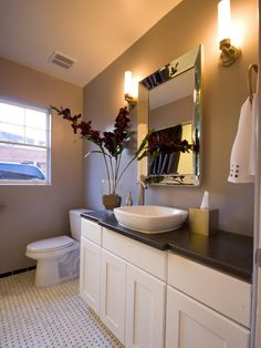 Black-and-white marble tile floors, silver-blue walls and charcoal gray concrete counters add trendy charm to this 1940s bathroom. A beveled mirror and wall sconces add glamour above the white vanity and vessel sink.