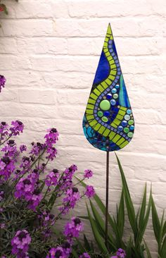 Hand crafted glass garden mosaic- A Pinch of Summer- A ever popular mixture of blue and green glass has been used in this design to evoke the blue sky and lush green vegetation of  British Summertime. Tear-drop shape. Serpentine design. A Pinch of Summer colour palette Approx size: 17cm x 40 cm Mounted onto a 1m metal pole which will rust naturally to give a rustic feel.