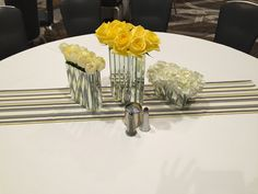 elegant mirror paneled vases as a suggestion to use only the short ones and line the tables.