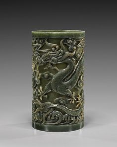 Very finely carved, Chinese spinach jade brushpot; of tall slim cylindrical form: with design of writhing five-clawed dragons amid clouds with a flaming pearl, and above waves around the base; H: 8 1/2""