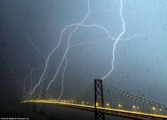 """Eight bolts of lightning hit the iconic Bay Bridge in San Francisco in a spectacular once in a lifetime moment captured by photographer Phil McGrew"""
