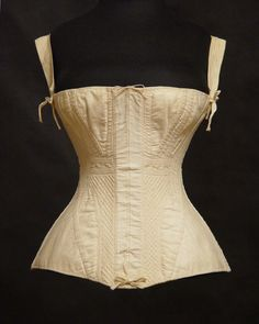 An incredible original 1830s ladys ivory sateen corset with its original blue steel busk in its front pocket.   Elaborately hand quilted and embroidered, top stitch reinforced, with woven braces tied in place, and at the busk pocket.   A drawstring cord at the top front and early ringed brass eyelets at the lace up back closure.
