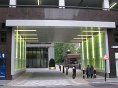 Vertical, glowing strips of light were designed to lead the eye upwards. Exterior Lighting, Lighting Design, Glow, Curtains, London, Eye, Architecture, Street, Home Decor