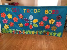 our daisy troop banner. the girls cut out their hands for the grass. we used foam flowers and had each girl decorate their own.