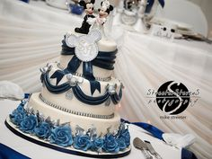 Beautiful Disney-themed wedding cake..there are certain parts of this that I like. I do like the ribbon with the silver Mickey's at the tops of the ribbons...2nd layer only.