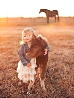 Little girl hugging baby horse, best pals.