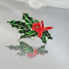 This #vintage Christmas holly brooch is absolutely gorgeous!  It features a green and red holly branch with red holly berries.  Beautiful glossy enamel and beads.  Rolling C... #ecochic #etsy #jewelry #jewellery #mistletoe