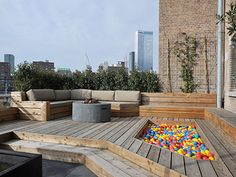 how to arrange a terrace with a wooden deck, a concrete pitfire, cushons and bench aaaand... a pool of balls! I absolutly need this #outdoorliving