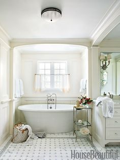 Clean white master bathroom with a romantic tub.
