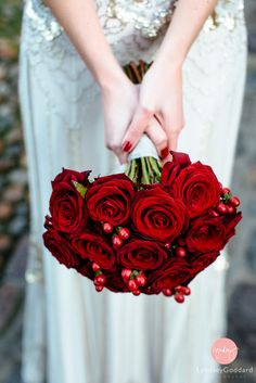 My DIY hand-tied winter bridal bouquet of red roses and hypericum berries