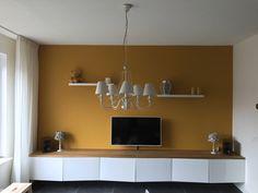 Woonkamer, zwevend tv-meubel, hoogglans wit, ikea besta kasten, okergeel op de muur, histor, verguld