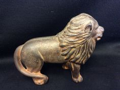 CAST IRON LION BANK WITH ONE FLAT HEAD SCREW. SOLID CONDITION, NICE COLLECTIBLE BANK. 4H X 4W