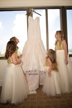 Photo by Michelle Lawson Photography. This is such a sweet picture. My junior bridesmaids and flowergirls were admiring my Maggie Sottero designer dress hanging in the window. My bridal party had custom made gold sequin tops, & floor length dresses #wedding #weddingideas #gettingdressed #weddingdress  #juniorbridesmaid #flowergirls #weddingdress #weddingdressideas #mstriciasfl #gettingready #blushweddingdress #pinkweddingdress #MaggieSottero #designerweddingdress #laceweddingdress