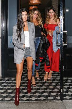 Kourtney Kardashian wearing denim cut-offs, booties, and an oversized blazer.