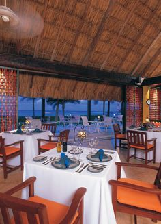 Dreams Cancun - Oceana Restaurant serving gourmet seafood under a giant thatched palapa.